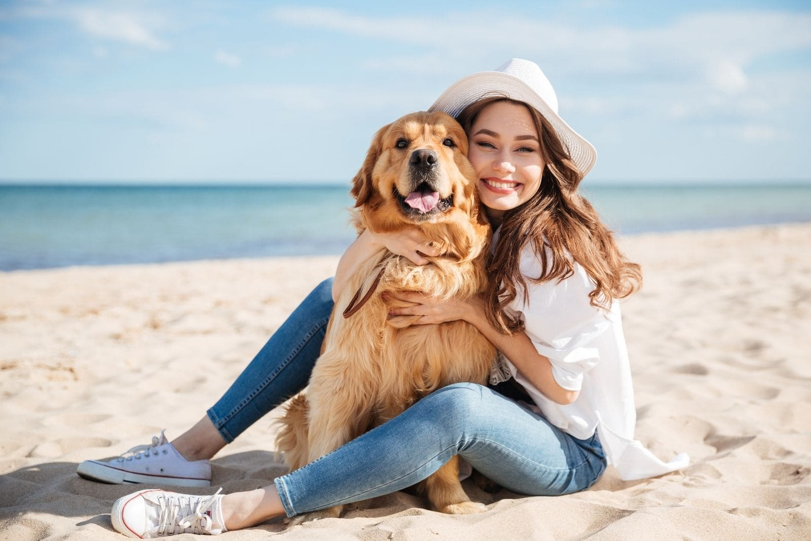 cheerful young woman sitting and embracing a dog in the beach during the day