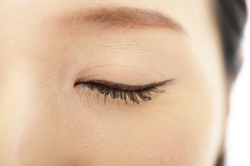 close up focus of a closed eye of an asian woman
