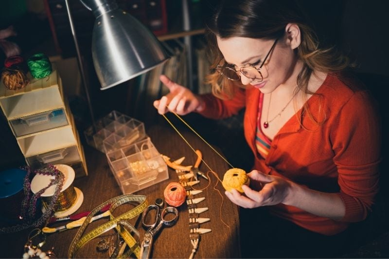 close up of a crafty woman making jewelry inside the workshop