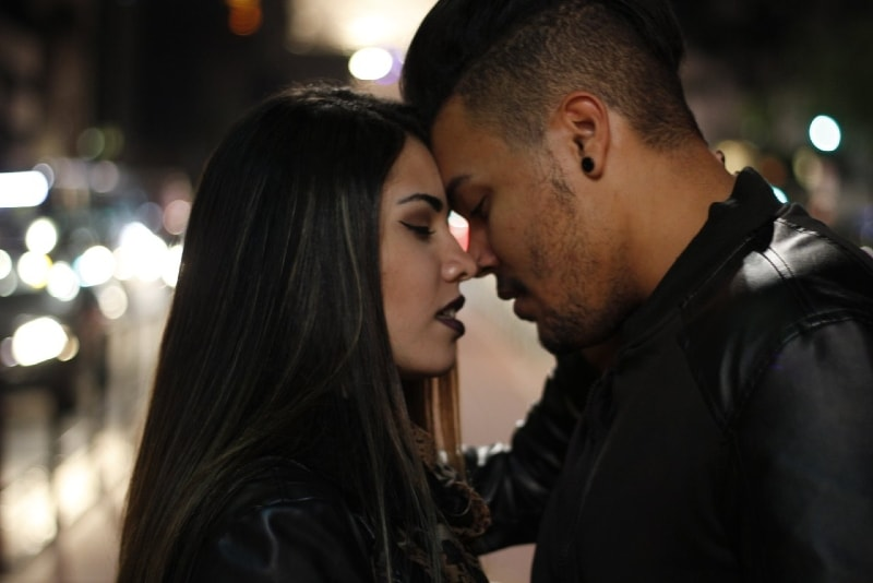 man in black jacket and woman about to kiss outdoor