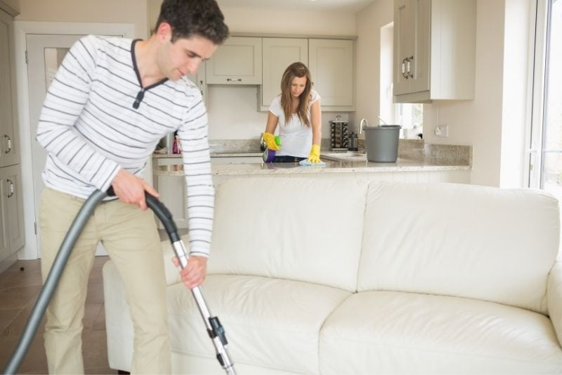 couple cleaning house together during the day