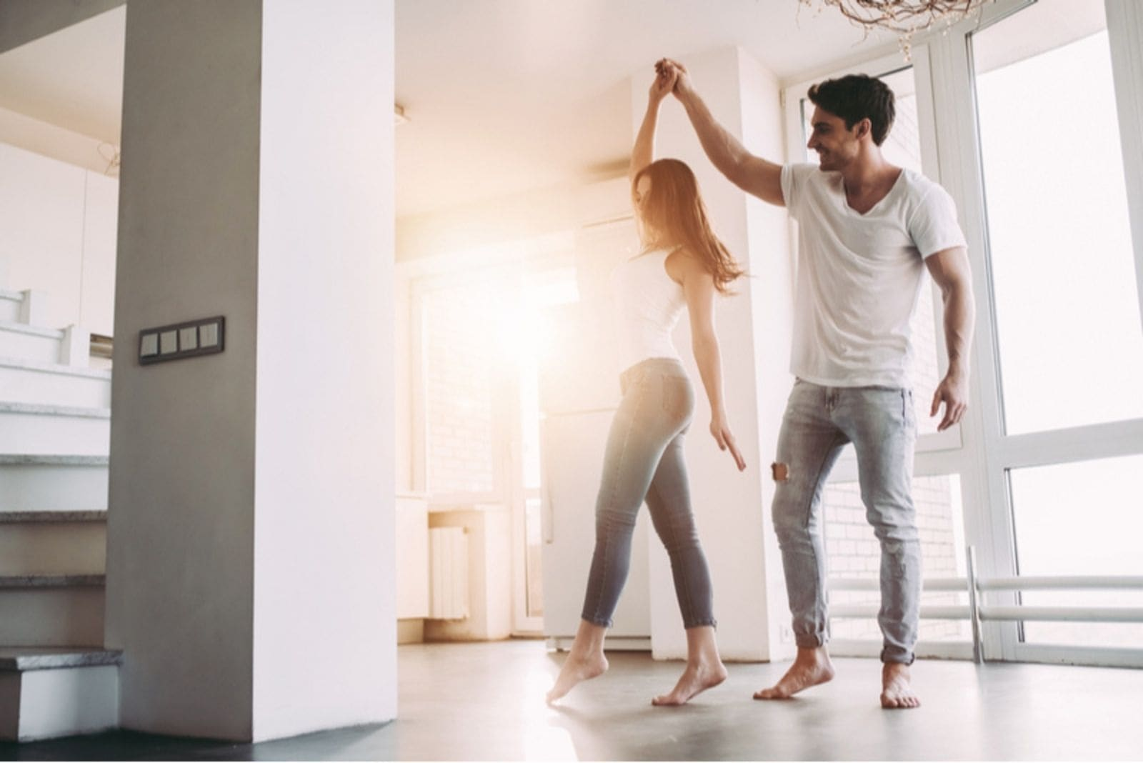 couple dancing around inside an empty room wearing white top and denim jeans