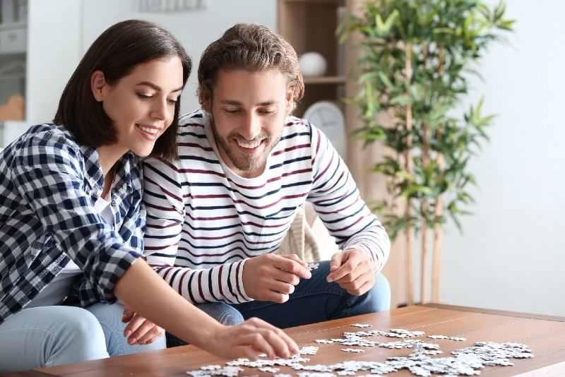 man and woman doing jigsaw puzzle at home