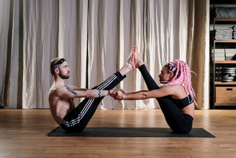 man and woman doing yoga on black mat