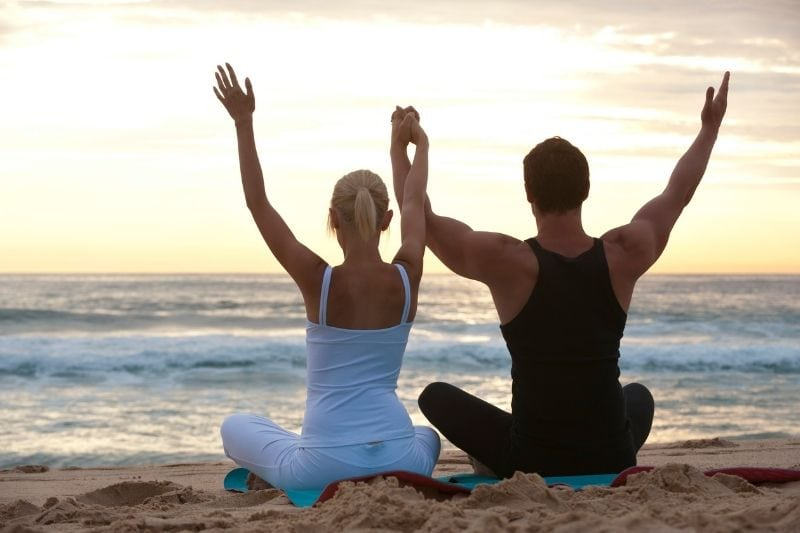 couple doing yoga raising their hands in the air facing the sea
