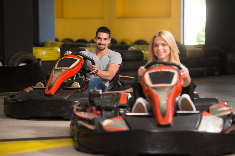 couple driving go-kart car in playground racing track