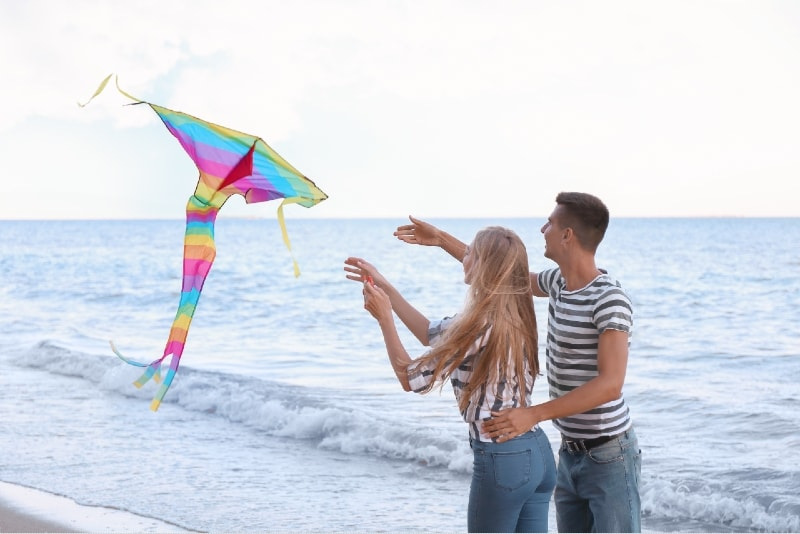 man and woman flying kite near sea