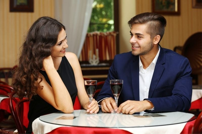 couple having wine during a dinner date inside a restaurant