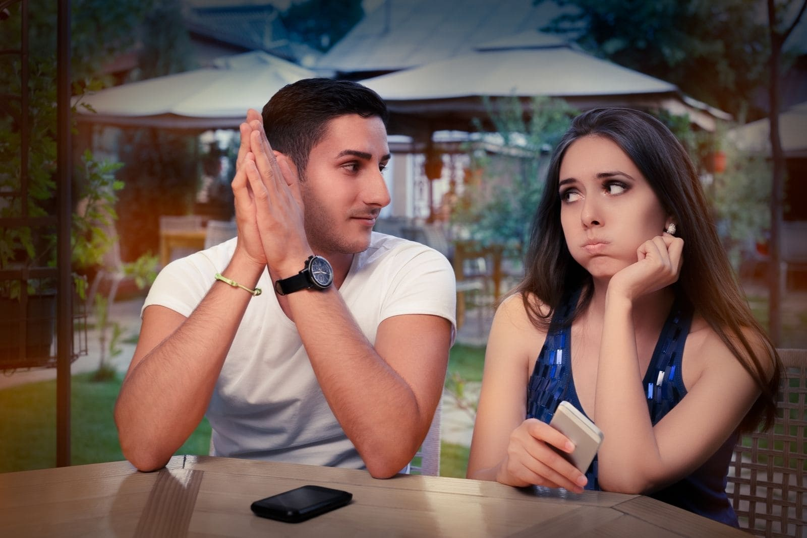 couple having problem with smartphone in an outdoor cafe with woman in disbelief expression