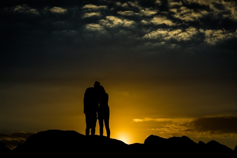 man and woman holding hands during sunset