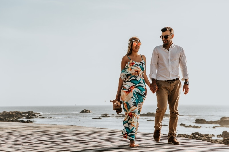man and woman holding hands while walking near sea