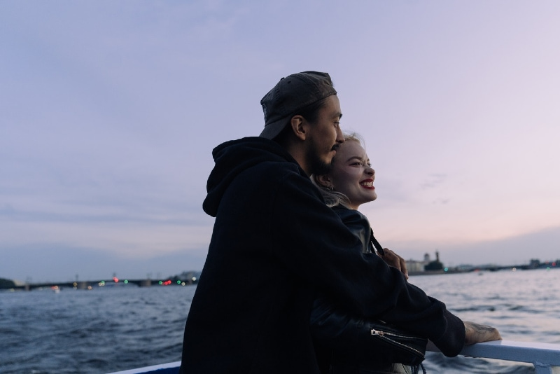 man and woman hugging while standing on boat