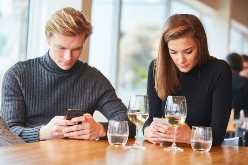 couple is silent with smartphone in their hand while waiting for ther food dining in a restaurant