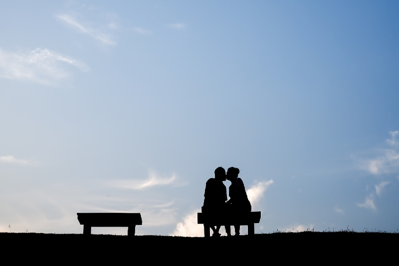 man and woman kissing while sitting on bench