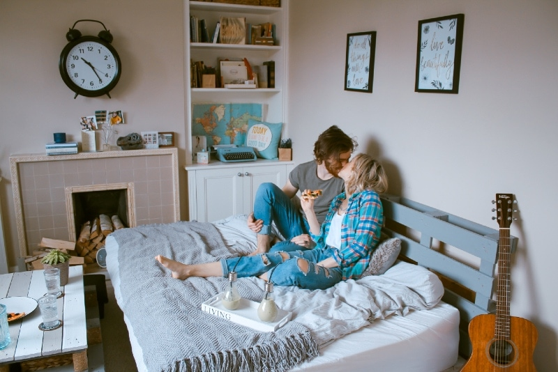man and woman kissing while sitting on bed