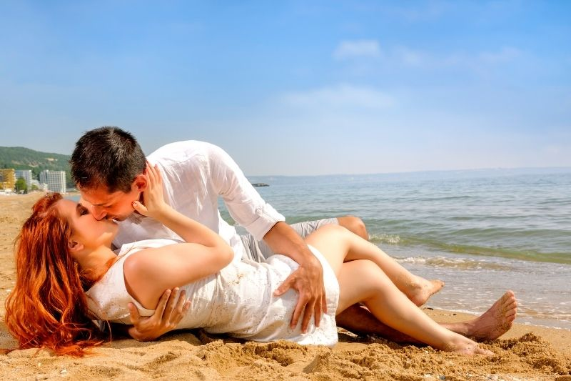 couple kissing lying in the beach in the day