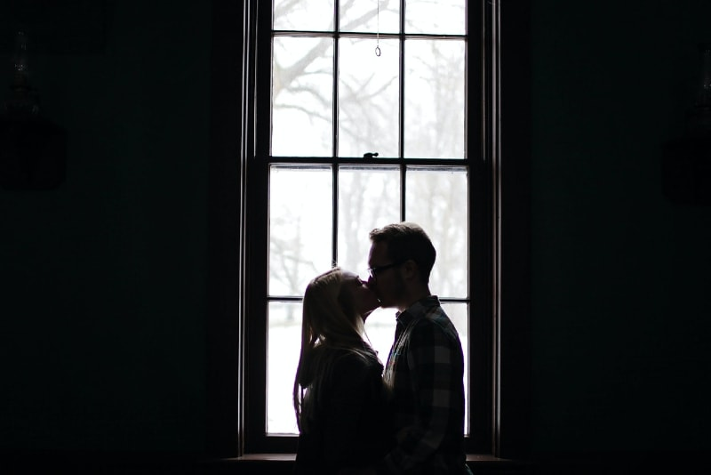 man and woman kissing near window