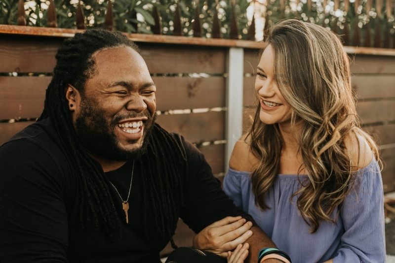 man and woman laughing while sitting outdoor