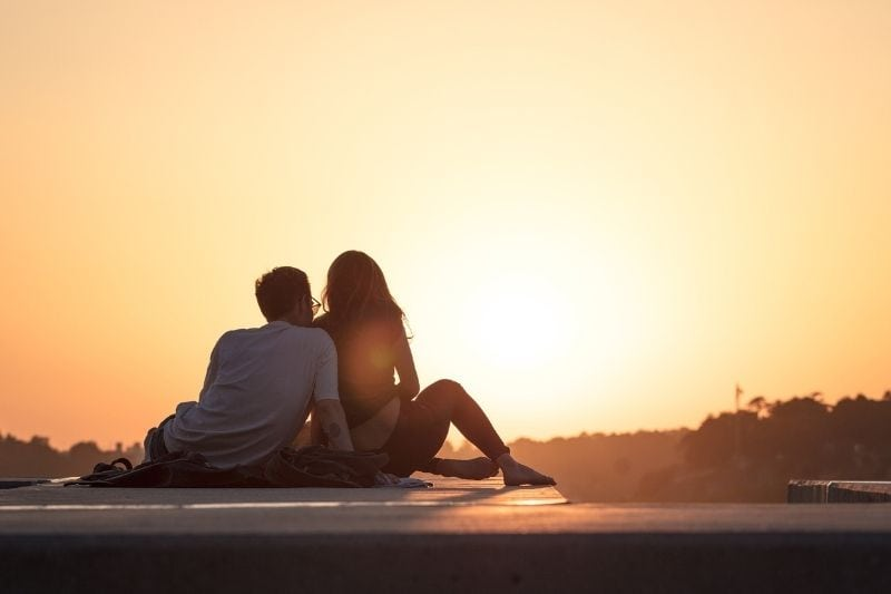 couple looking at sunset sitting on the rooftop