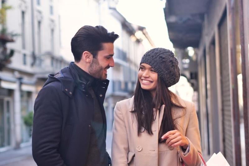 man in black jacket and woman making eye contact while standing outdoor