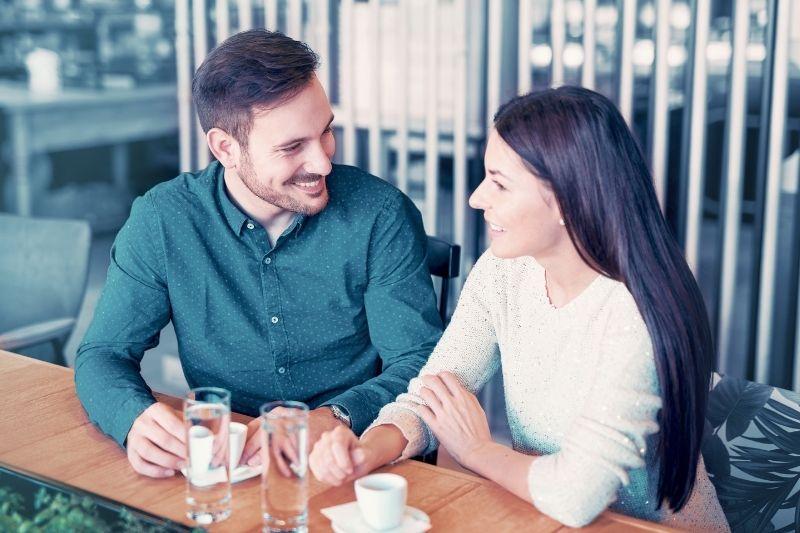 couple on coffee break talking in a cafe