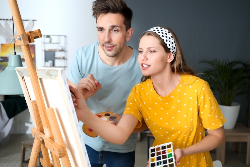 woman in yellow t-shirt and man painting indoor