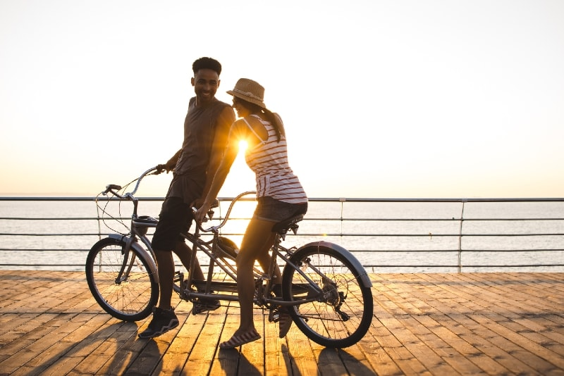 man and woman riding bicycles near sea during sunset