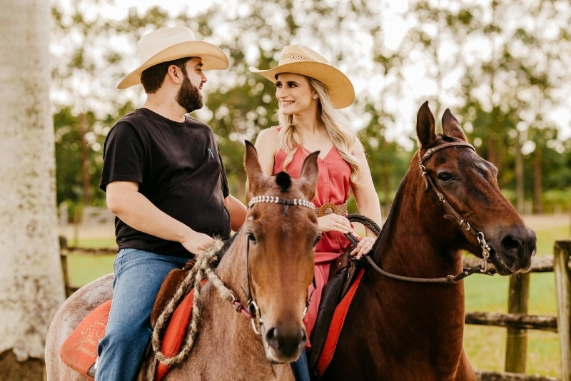 man and woman making eye contact while riding horses