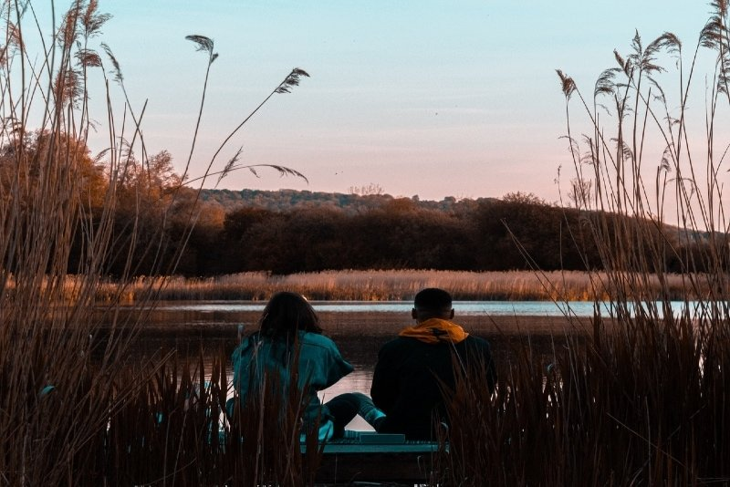 man and woman sitting near water during golden hour