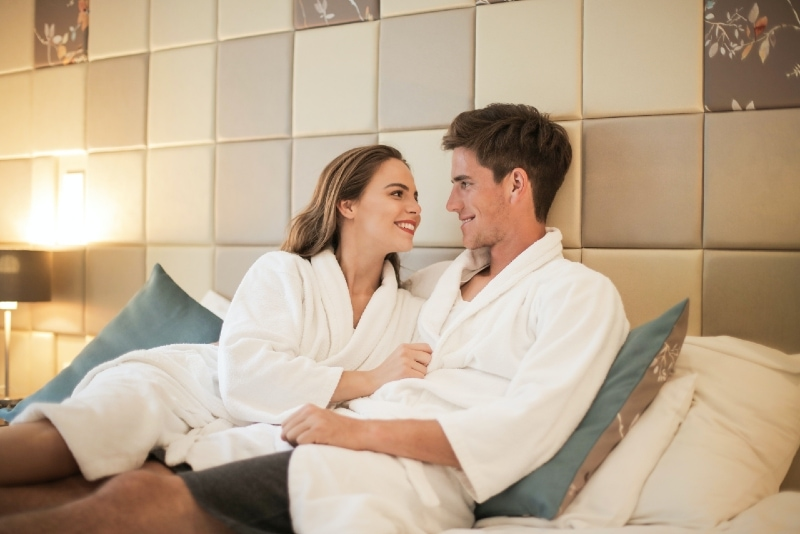 man and woman in white robes sitting on bed