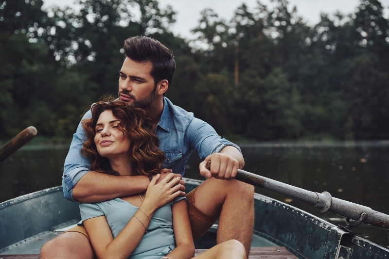 man hugging woman while sitting on boat