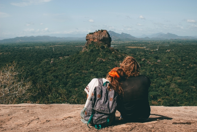 woman with gray backpack and man sitting on cliff