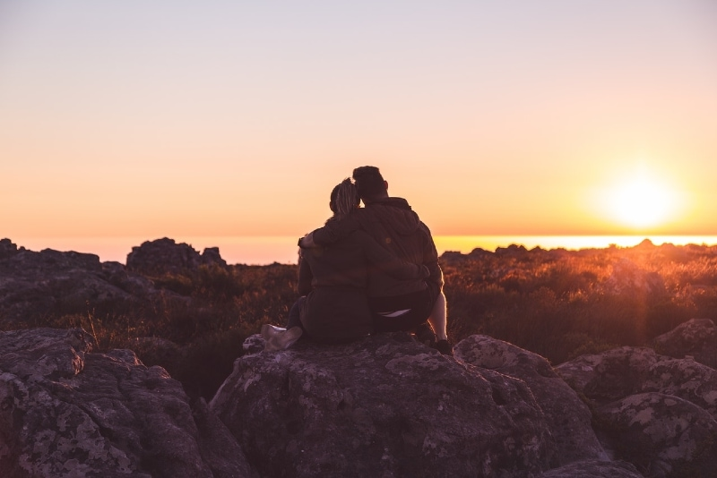 man and woman sitting on rock looking at sunset
