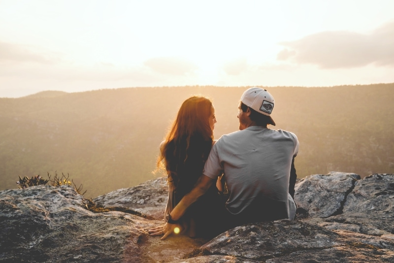 man in gray t-shirt and woman sitting on rock