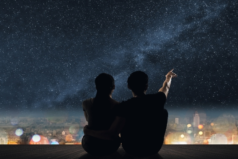 man and woman sitting on rooftop watching stars