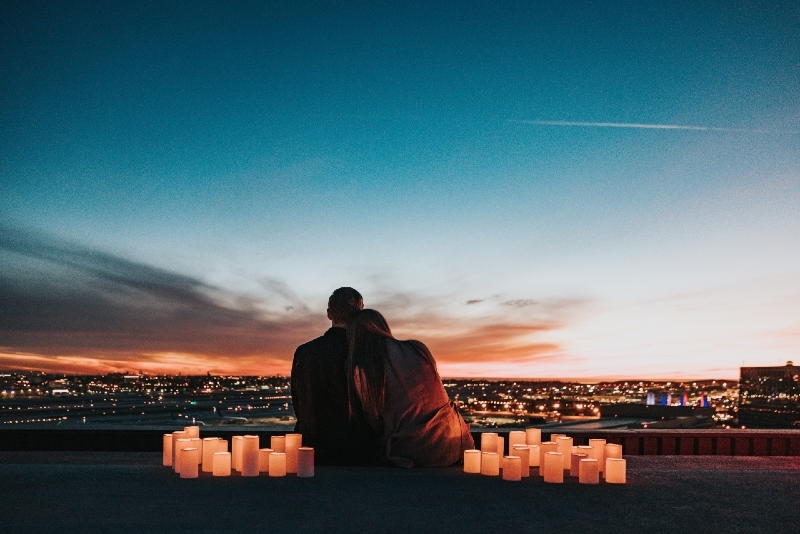 man and woman sitting on rooftop looking at city