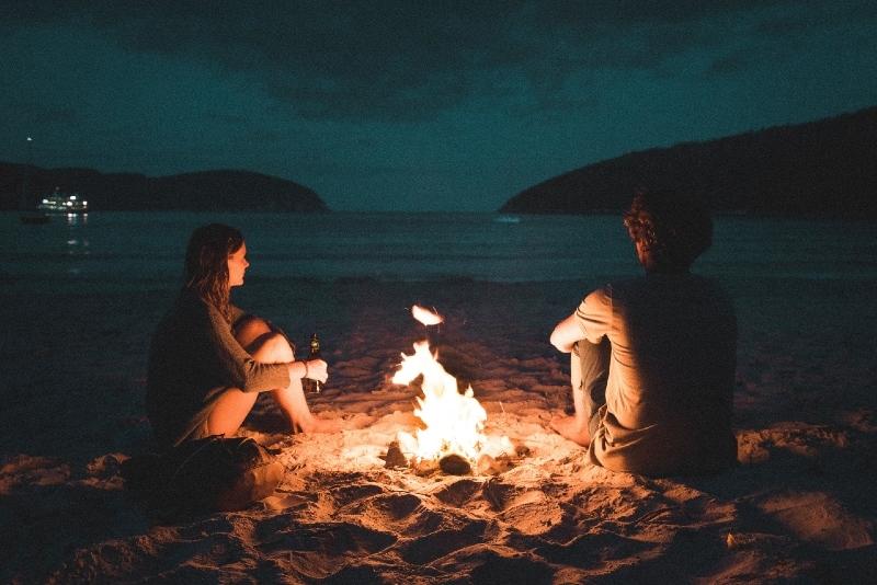 man and woman sitting on seashore near bonfire