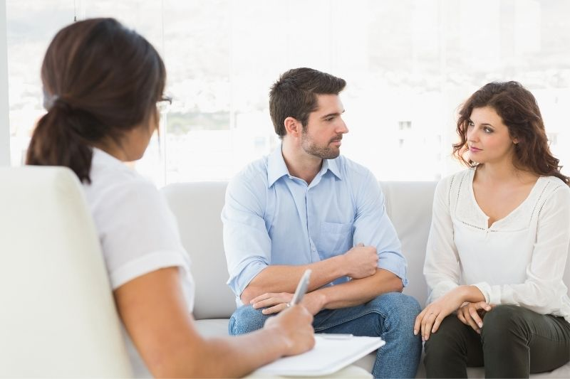 couple sitting on sofa talking to their marriage counsellor