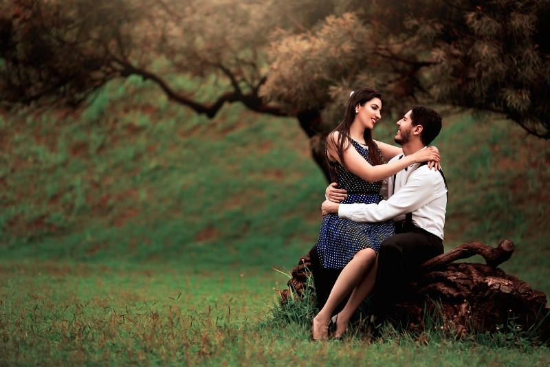 man and woman hugging while sitting on tree trunk
