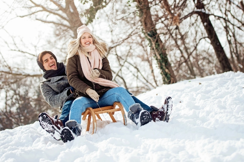 couple sliding on a sledge in winter day
