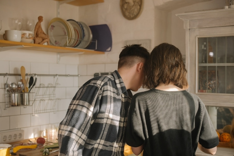 man in gray checked shirt standing near woman in kitchen