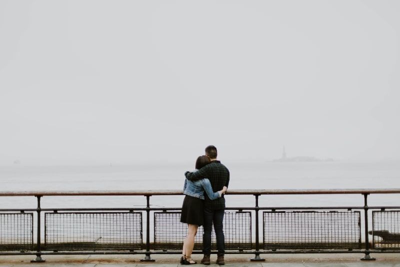 man and woman hugging while standing near fence