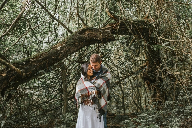 man and woman wrapped with blanket standing near tree