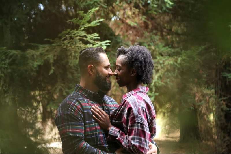 man and woman hugging while standing near tree