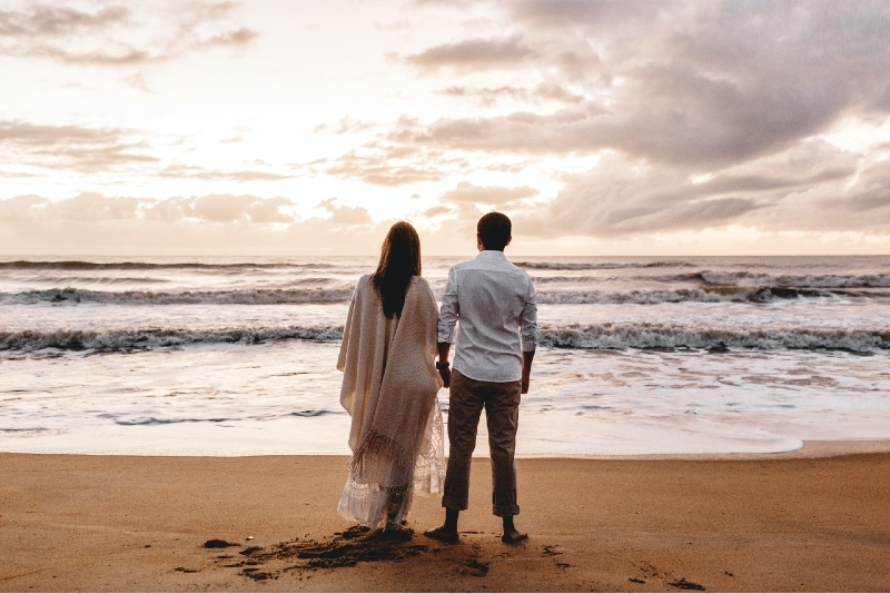 man and woman holding hands while standing on beach