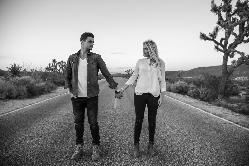 man and woman holding hands while standing on concrete road