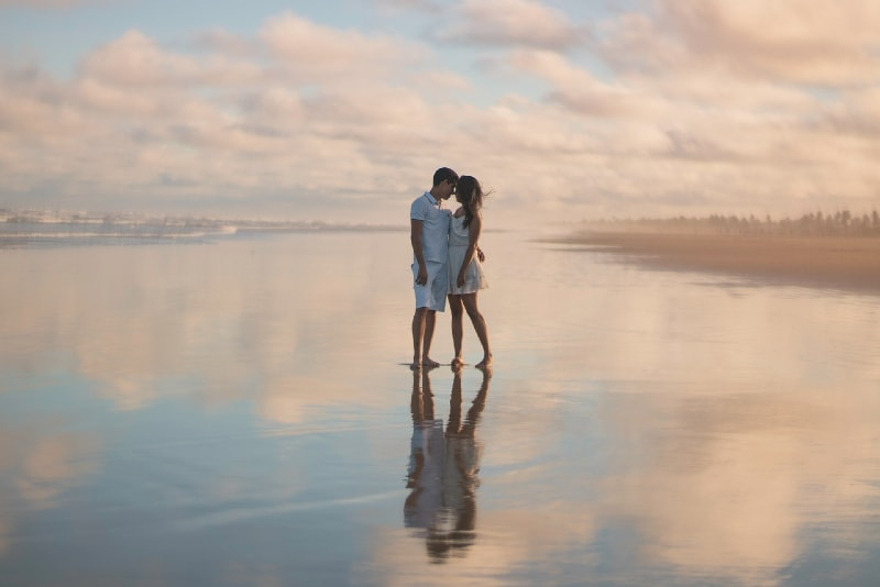 man and woman hugging while standing on water