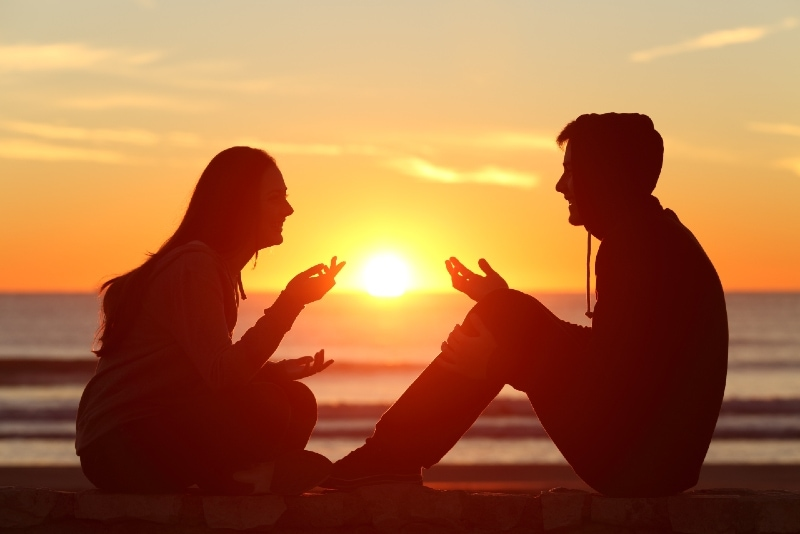 man and woman talking while sitting outdoor during sunset