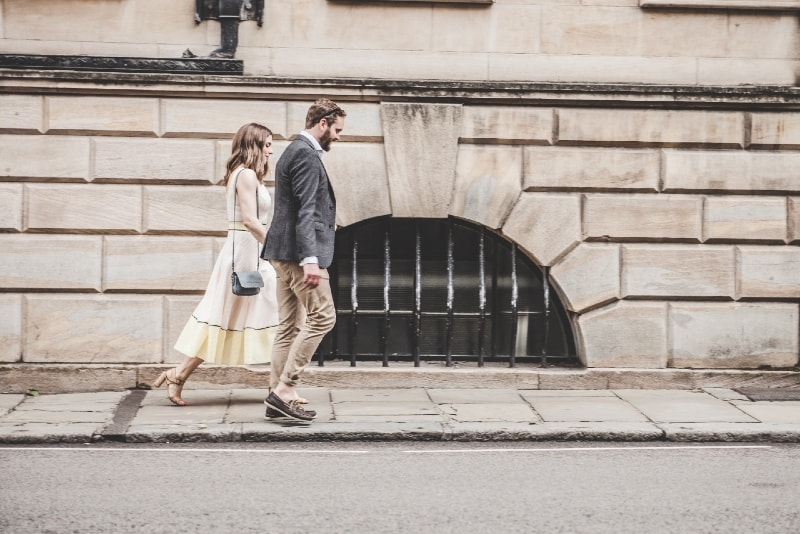 man and woman holding hands while walking beside road