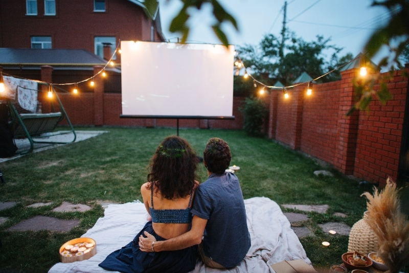 man and woman watching movie on projector screen outdoor